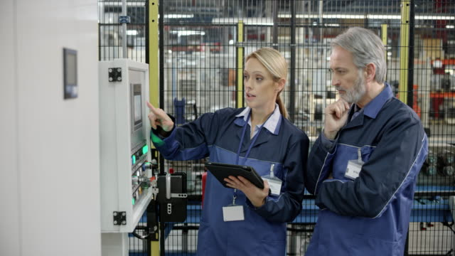 male and female factory employee talking about the values shown on the machine's lcd screen - occupazione industriale video stock e b–roll