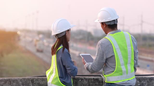 ingegnere caposofase maschio e femmina discutere e utilizzare tablet digitale con sfondo autostradale - cantiere di costruzione video stock e b–roll