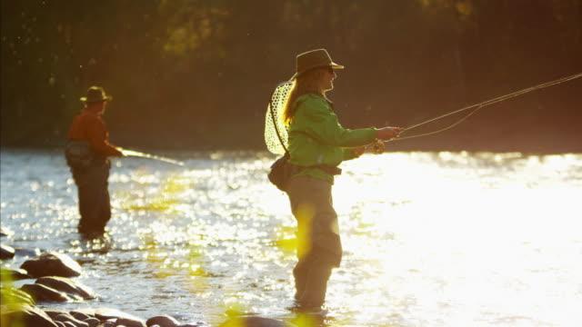 Male and female Freshwater fly fishing sunrise Canada