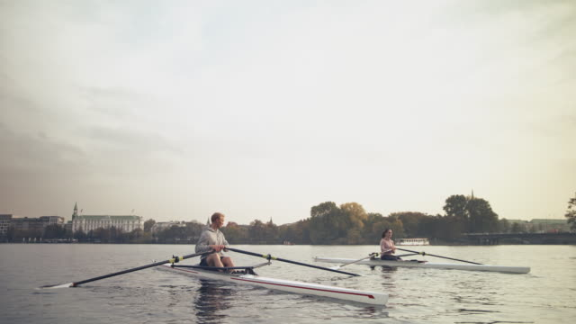 male and female friends resting on rowboat - sculling video stock e b–roll