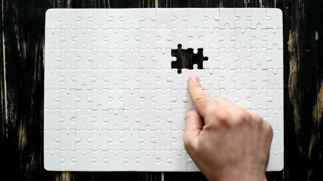 male and female hands  adds white puzzle - puzzle stock videos and b-roll footage