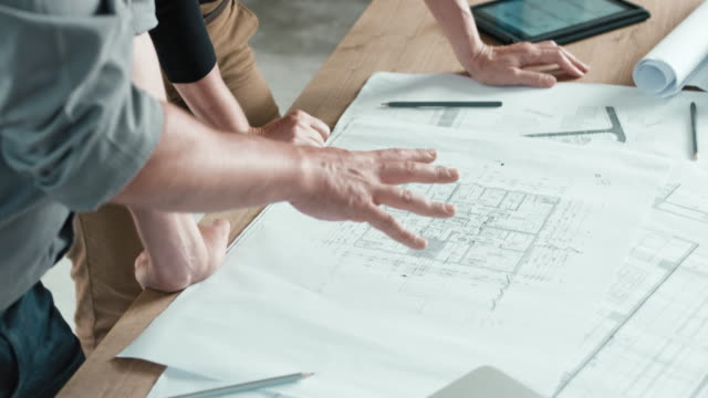 male and female hands pointing out details on the construction plan set on the table - architetto video stock e b–roll