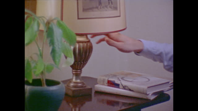 1974 male and female hands turn off lights - elektrische lampe stock-videos und b-roll-filmmaterial
