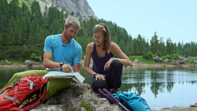 male and female hiker checking the map sitting by the lake high in the mountains - mid adult stock videos & royalty-free footage