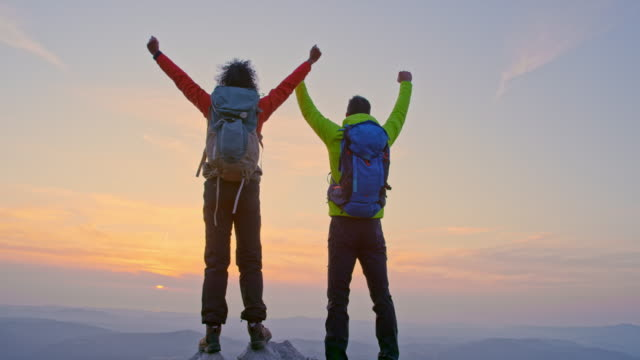 slo mo male and female hiker raising their hands on the mountain top as the sun sets behind the mountains - efficiency stock videos & royalty-free footage