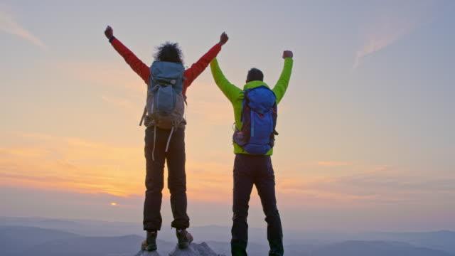 stockvideo's en b-roll-footage met slo mo mannelijke en vrouwelijke wandelaar die hun handen op de bergbovenkant opheffen aangezien de zon achter de bergen ondergaat - effectiviteit
