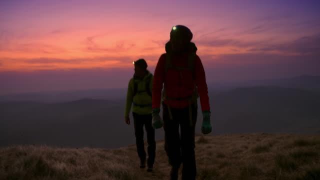 vidéos et rushes de randonneur mâle et femelle de ts marchant vers le haut de la montagne avec des phares dessus au crépuscule - lampe frontale