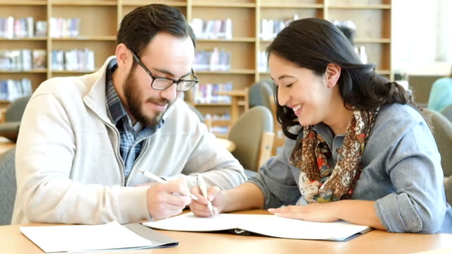 vídeos de stock, filmes e b-roll de homem e mulher hispânica adulto estudantes universitários sorrindo enquanto eles estudam juntos na biblioteca - aluno mais velho