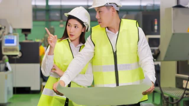 男性と女性の産業エンジニアは、重工業製造業に立ちながらプロジェクトの設計図を見ます。技術,産業,科学,イノベーション,産業4.0,stemの女性自動化 – 大規模な産業コンセプト。 - 説明する点の映像素材/bロール