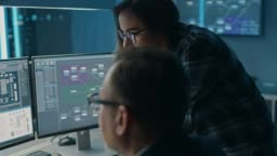 Male and Female IT Engineers / Programmers Having Discussion about Code Shown on Desktop Computer Displays. Displays Show Software Development / Code Writing / Website Design / Database Architecture