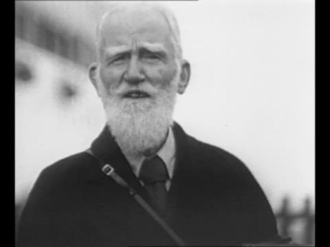 male and female journalists make notes while in attendance with playwright george bernard shaw / shaw speaks at event / sot shaw cracks quip while... - ジョージ バーナード ショー点の映像素材/bロール