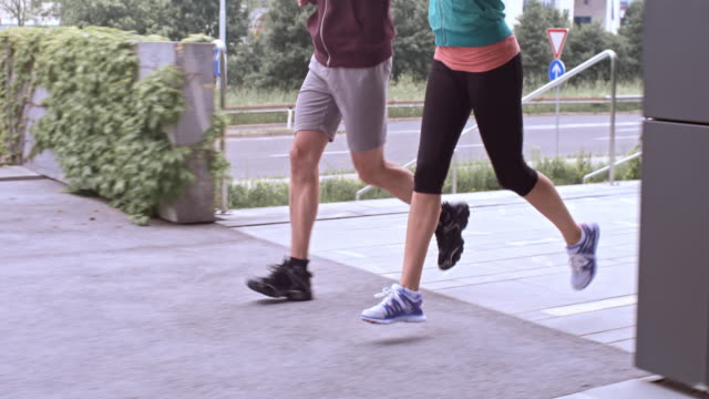 SLO MO Male and female legs running in the city