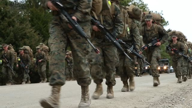 stockvideo's en b-roll-footage met male and female marines participate in a 10 kilometer hike carrying 55 pound packs at marine combat training on february 22 2013 at camp lejeune... - army