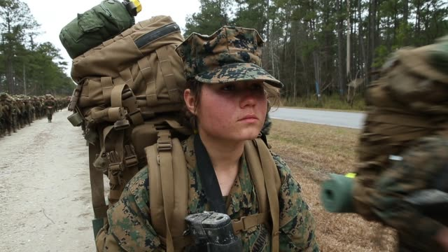 Male and female Marines resume a 10 kilometer hike carrying 55 pound packs after stopping for a water break at Marine Combat Training on February 22...