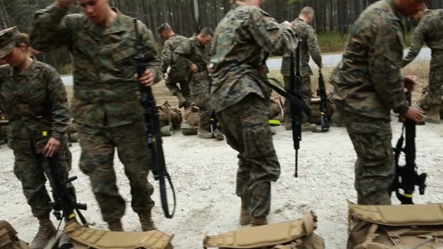 Male and female Marines stop for a water break during a 10 kilometer hike carrying 55 pound packs at Marine Combat Training on February 22 2013 at...