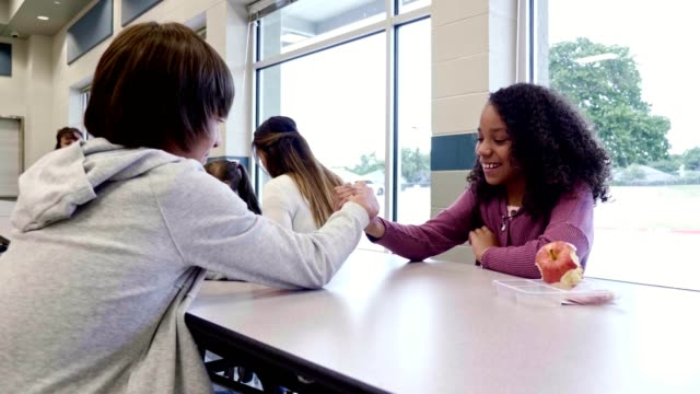vídeos de stock e filmes b-roll de male and female middle school students arm wrestle during lunch - aluna da escola secundária