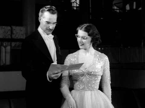 a male and female model pose in evening wear while modelling spectacles 1953 - evening wear stock videos & royalty-free footage