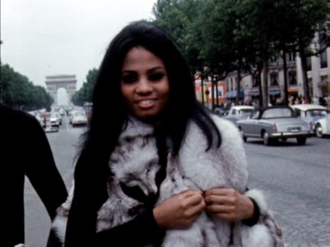 vidéos et rushes de male and female models pose for the camera on the champs elysees wearing fur stoles scarves and hats. 1970. - châle