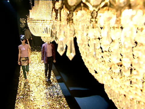 ha ms male and female models walking up and down gold foil runway under row of chandeliers at b&c european style fashion show/ belgrade, serbia  - hand an der hüfte stock-videos und b-roll-filmmaterial