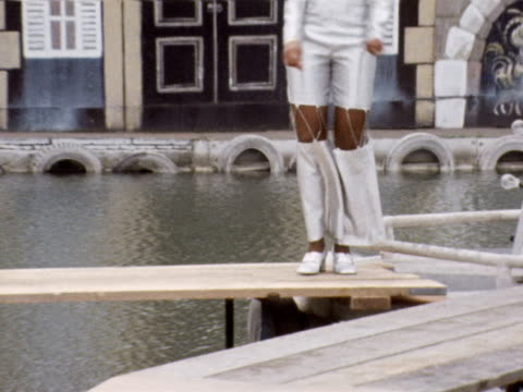 male and female models wearing the latest fashions by john stephen dance on wooden gangplanks over a pool of water at an outdoor fashion show 1969 - fashion collection stock videos & royalty-free footage