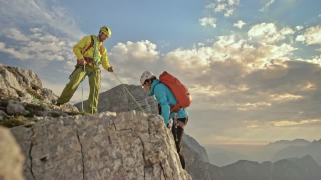 male and female mountaineer climbing to the mountain top with help of climber at the top - piccolo gruppo di persone video stock e b–roll