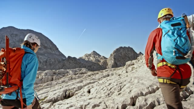 male and female mountaineer walking on a rocky mountain and talking - slovenia stock videos & royalty-free footage