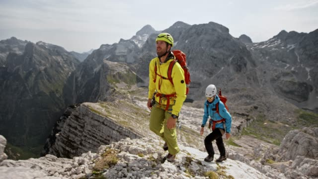 Male and female mountaineer walking up a rocky mountain ridge in sunshine