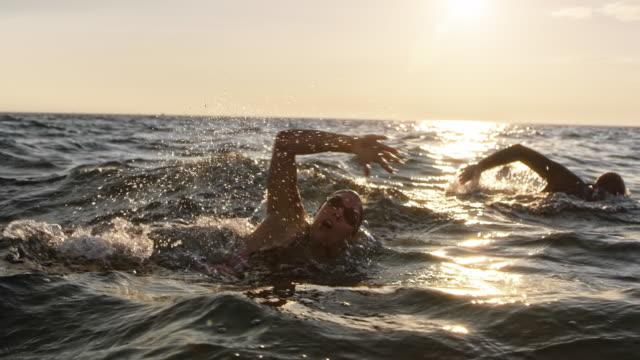 vidéos et rushes de slo mo mâle et femelle eau libre nageur natation front rampent en mer sous le soleil - bras humain