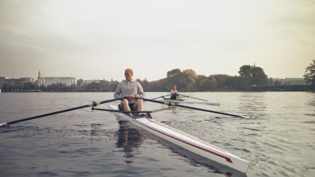 male and female resting on rowboat in river - sculling video stock e b–roll