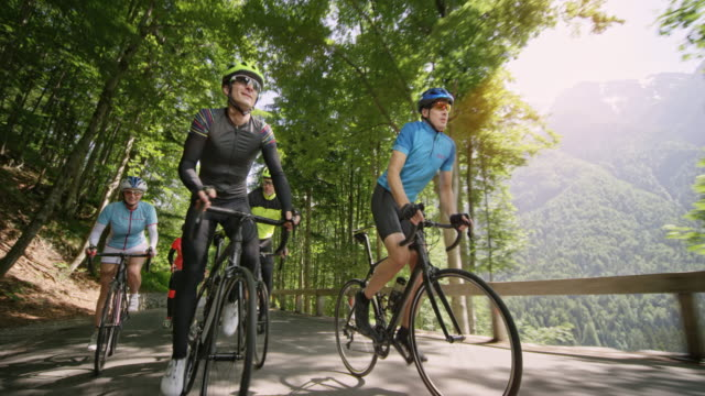 vídeos de stock e filmes b-roll de male and female road cyclists riding on a nice asphalt road in sunshine - 30 39 anos