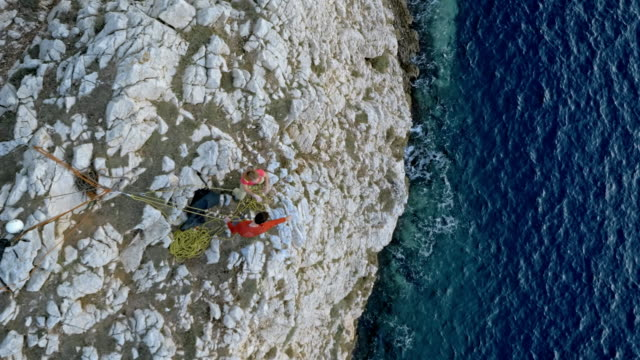 aerial male and female rock climber giving each other a hug as they reach the top of the steep cliff above the sea - steep stock videos & royalty-free footage