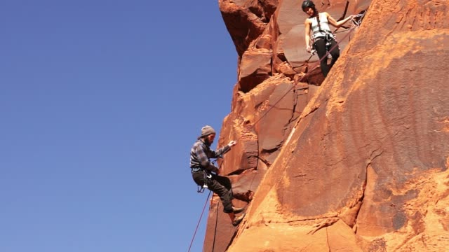 male and female rock climbers in moab - imbracatura di sicurezza video stock e b–roll
