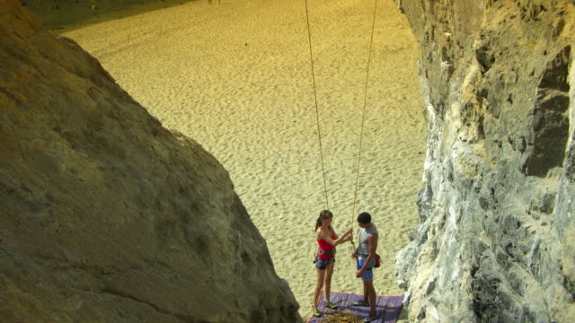 ha ms male and female rock climbers standing on beach, woman checking man's rope and harness / krabi, thailand - lead stock videos and b-roll footage