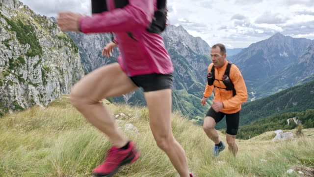 slo mo ds male and female runner ascending a mountain up a grassy and steep mountain side - shorts stock videos & royalty-free footage