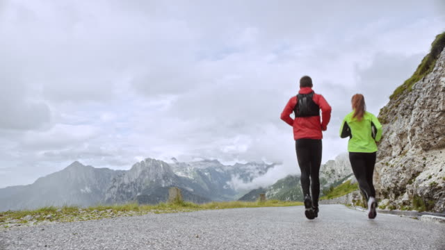 ds male and female runner descending the mountain on an asphalt road overlooking the nearby peaks - redhead stock videos & royalty-free footage