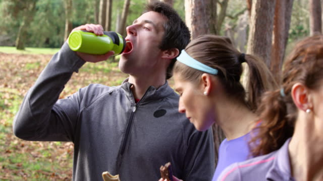 MS Male and female runner eating energy bars and drinking water after run in park with friends