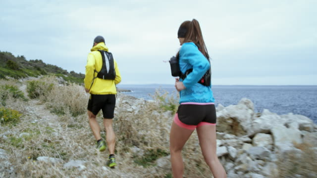male and female runner running along a rugged beach on a rocky trail in bad weather - hat stock videos and b-roll footage