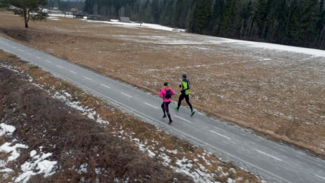 AERIAL Male and female runner running on walkway on a cold winter day