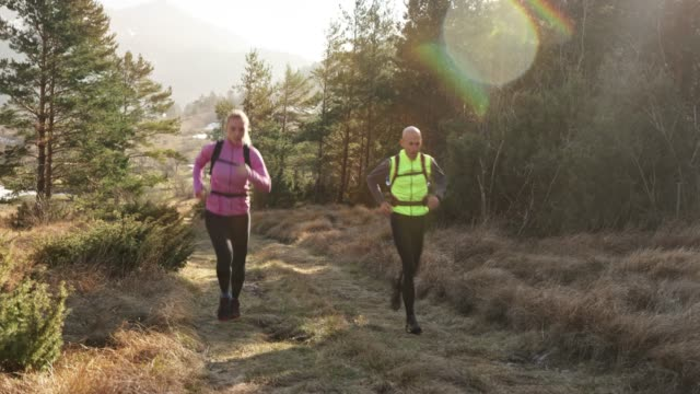 Male and female runner running up a forest trail on a sunny day