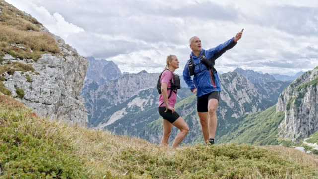 DS Male and female runner talking about the trails as they stand on a mountain meadow and pointing into the distance