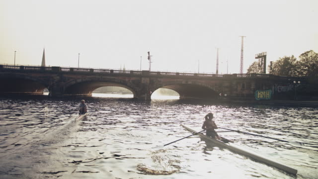 male and female sculling boats in river - sculling stock videos & royalty-free footage