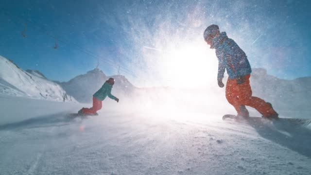 slo mo ts male and female snowboarder riding down a sunny slope and snow particles flying in the air - ski holiday stock videos & royalty-free footage