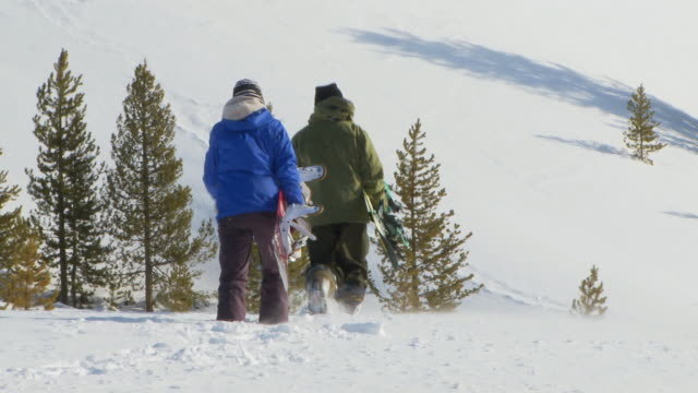 Male and female snowboarders hike through back-country powder / Blaine County, Idaho, United States