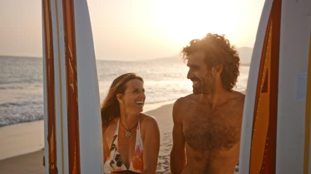 Mannelijke en vrouwelijke surfer houden hun surfplanken op het strand bij zonsondergang en lachen
