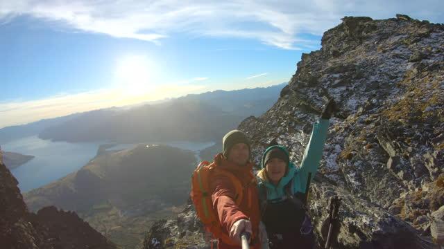 male and female taking selfie mountain lake wakatipu - recreational pursuit stock videos & royalty-free footage