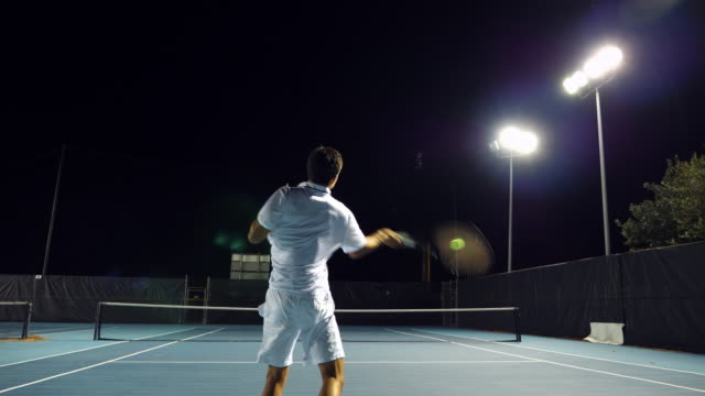 ms male and female teenage tennis teammates practicing on outdoor court at night - tennis stock videos and b-roll footage