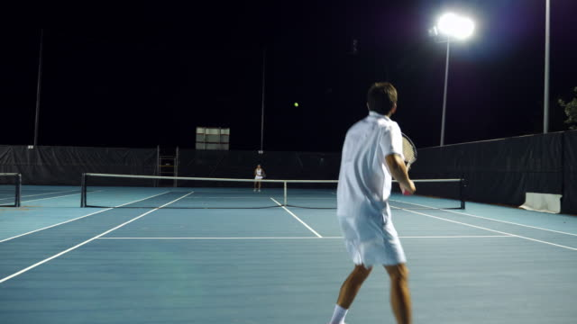ms male and female teenage tennis teammates practicing on outdoor court at night - teenage boys stock videos & royalty-free footage