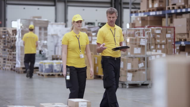 DS Male and female warehouse employee discussing packages in the warehouse while walking around