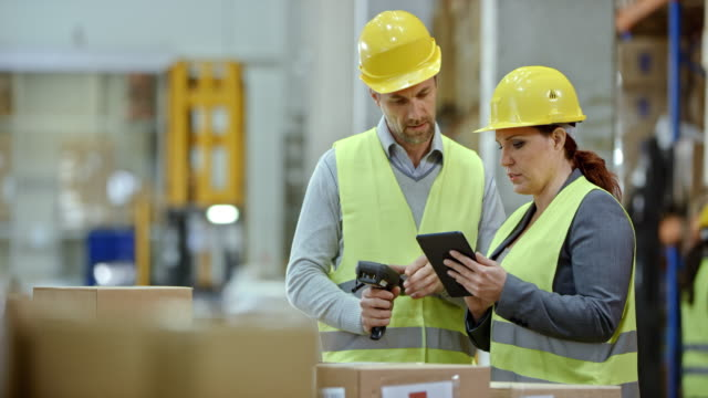 male and female warehouse supervisors talking about the inventory check in the warehouse - deposito video stock e b–roll
