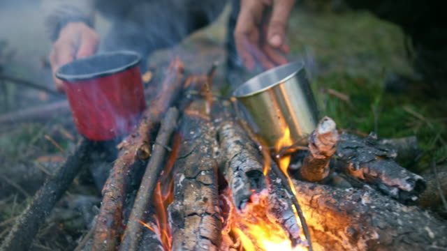 male and female wilderness survival expert drinking tea while sitting by the campfire - wilderness stock videos & royalty-free footage